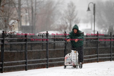 Kevin Bartram | Staff Roy Hinze II makes his way home with groceries as snow falls on Thursday in Bristol.