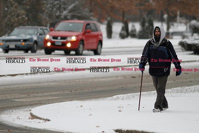 Kevin Bartram | Staff Tyler Grandbois walks along Memorial Boulevard as snow falls on Thursday in Bristol.