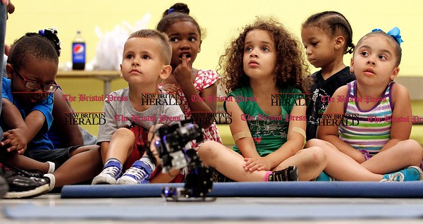 Kevin Bartram | Staff Children at the Boys and Girls Club watch as New Britain High School students demonstrate the robots they built as part of the Young Engineers program sponsored by the Boys and Girls Club and CCSU. The students built two robots over a four-day period.