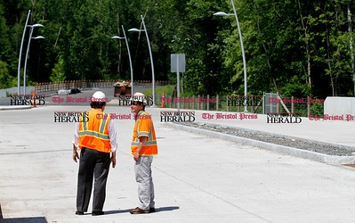 Kevin Bartram | Staff Michael Sanders, left, and Rich Symonds from the state Department of Transportation stand in the Cedar Street station as CTFastrak officials tour sections of the busway in New Britain and Newington on Monday to check the progress of construction.