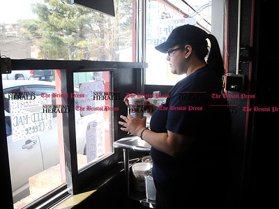 3/1/2014 Mike Orazzi | Staff Alycia Jandreau works the drive thru at Frankies on Route 6 in Bristol Saturday. The local hot dog restaurant is celebrating 30 years under the same ownership.