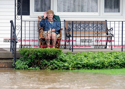 9/8/2011 Mike Orazzi | Staff Helen Lamothe waves from her front porch on  Tulip Street Thursday morning as the Pequabuck River spilled its banks once again after heavy rains.