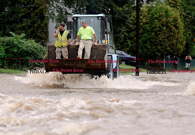 9/8/2011 Mike Orazzi | Staff Steve Baron (left) and Joe Maghini (right) get a ride through flood water on a front end loader driven by fellow D'Amato Construction employee Luis Siera as Pequabuck River flood waters fill the area near Tulip and Barnes Street in Bristol on Thursday morning.