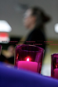 Kevin Bartram | Staff Purple candles sit on a table as a domestic abuse survivor speaks during a candlelight vigil at the Prudence Crandall Center in New Britain on Wednesday.