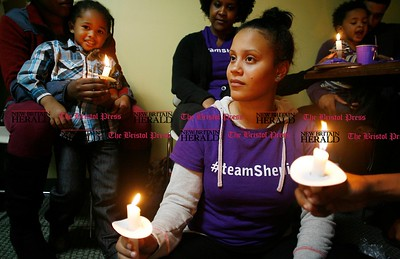 Kevin Bartram | Staff Ashley Walker holds a candle during a candlelight vigil at the Prudence Crandall Center in New Britain on Wednesday. Ashley's sister, Shenia Walker, was killed in Bristol in 2013.