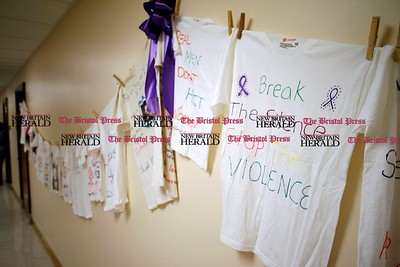 Kevin Bartram | Staff Shirts decorated with anti-domestic violence messages hang on a wall during a candlelight vigil at the Prudence Crandall Center in New Britain on Wednesday.