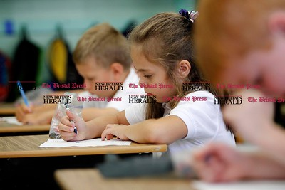 Kevin Bartram | Staff First grader Julia GHrabek works in class during the first day of school at Saint John Paul II School in New Britain on Tuesday.
