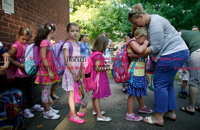 Kevin Bartram | Staff First grader Emma Porteus, 6, gets a hug from her mother Amy Porteus at the start of the first day of school at Frank T. Wheeler Elementary School in Plainville on Tuesday.