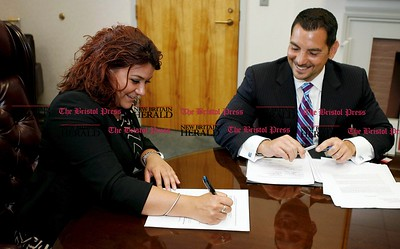 Kevin Bartram | Staff Corporation Counsel Gennaro Bizzarro, right, watches as Mayor Erin Stewart signs a contract with Costco on Tuesday at City Hall. A groundbreaking ceremony is scheduled for 10 a.m. Wednesday at Stanley Golf Course.