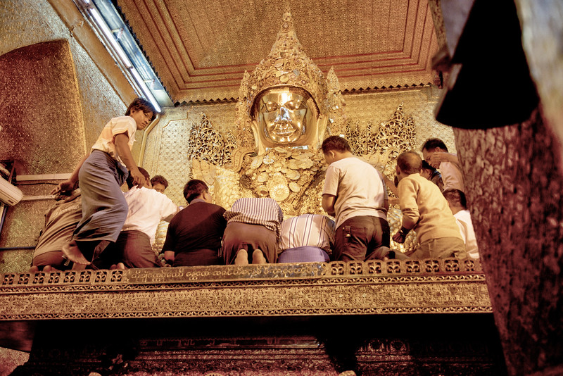 Pasting gold on the Buddha at Mahamuni Paya