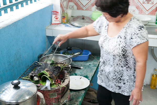 Ida grilling the rellenong bangus in banana leaves