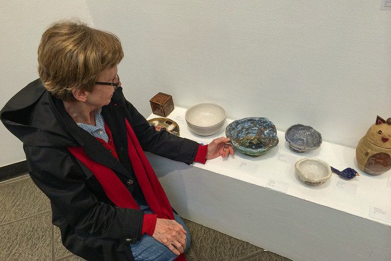 Wynda looking at Tace's bowl he made in a pottery class.