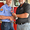 LCC President Tim Hetzner presents a patch from the Boone County (Illinois) Fire District to the Prescott Fire Department, home to the Granite Mountain Hotshots