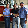 LCC President Tim Hetzner and volunteer firefighter Nathan Knuth from Cairo, Nebraska present a patch and t-shirt from the Cairo (Nebraska) Volunteer Fire Department to the Prescott Fire Department, home to the Granite Mountain Hotshots