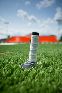 A spool of thread sits on the field