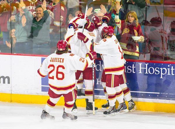 DU Pioneers players celebrate a goal in front of the fans.