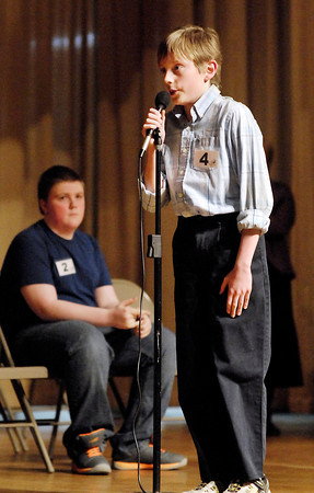 Tristan Hankins, of Highland Middle School, spells the winning word 'malformed' to become the Spelling Bee champion over runnerup Jeffery Krieg, of St. Mary Middle School in Anderson, who is looking on.