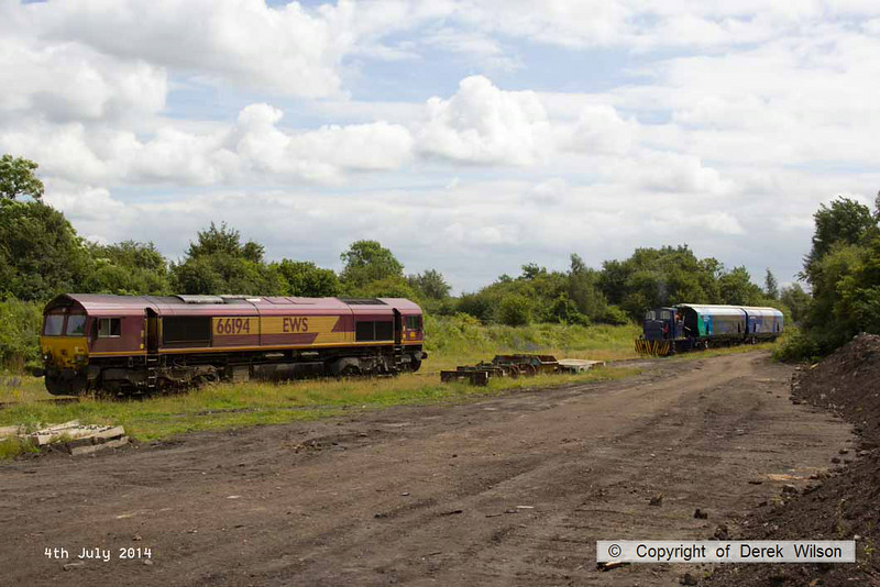 140704-007     WH Davis' Andrew Barclay 0-4-0DH no 499 is captured shunting biomass hoppers out of the yard, whilst DB Schenker class 66/0 no 66194 waits to push the hoppers down the branch. In all, nineteen hoppers were shunted out of the yard to make up the train.