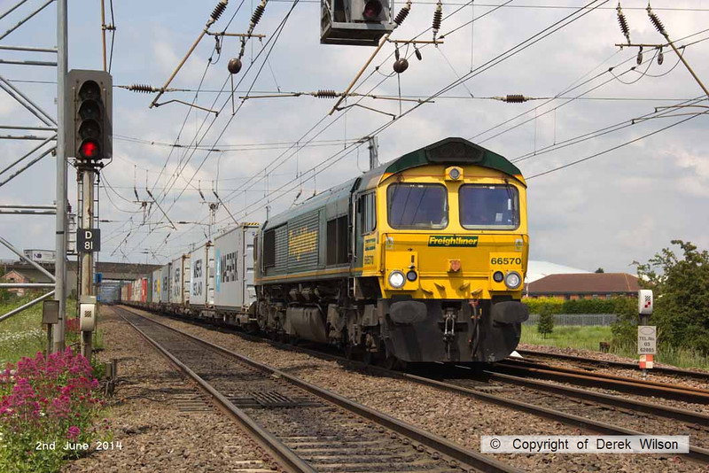 140602-061     Freightliner Heavy Haul class 66/5 no 66570 is seen on the up main, approaching Hatchet's Lane foot crossing, powering Intermodal 4L85, the 12.28 Doncaster Railport to Felixtowe North.