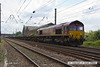140602-059     DB Schenker class 66/0 no 66143 is seen passing Hatchet's Lane foot crossing at Newark, powering 4E26, the 07.50 Dollands Moor to Scunthorpe, empty steel carrying wagons.