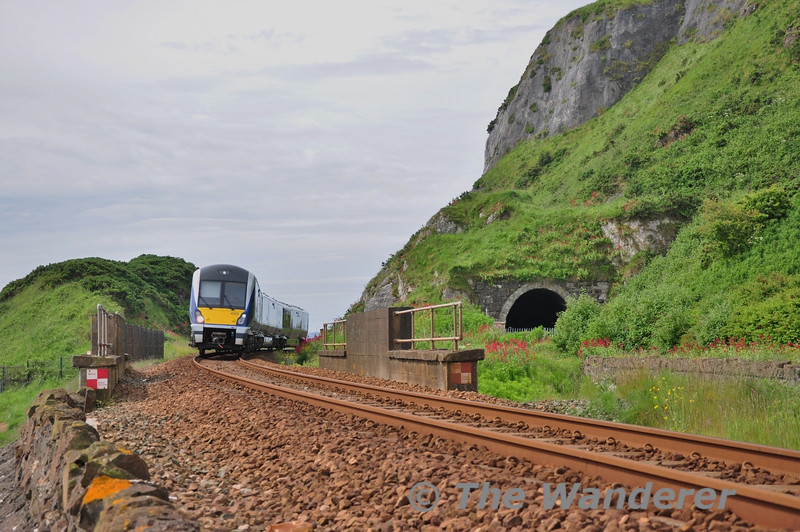 Previously the line south of Whitehead was double track before being singled. Up to the mid 1990's the single line operated through the tunnel to the right. Nowadays the single line operates on the formation of the former Up Line and skirts the cliff face. 4020 is pictured passing the former Tunnel with the 1015 Great Victoria Street - Whitehead. Thurs 12.06.14