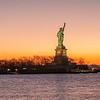 The silhouette of Statue of Liberty in New York City at sunrise
