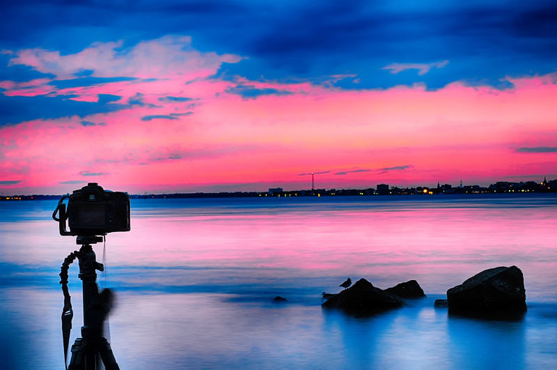 Dslr camera shooting on a beutiful seascape with blue red sky sunset