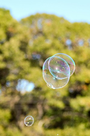 blowing bubble balloons on a field