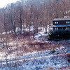 log cabin on a side of a mountain during winter months