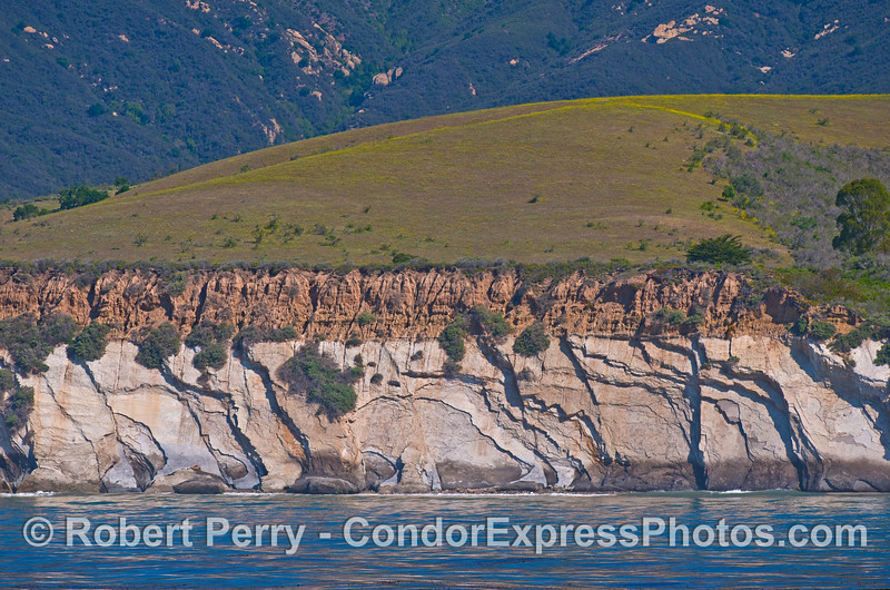 Sedimentary rock cliffs with fracture patterns.