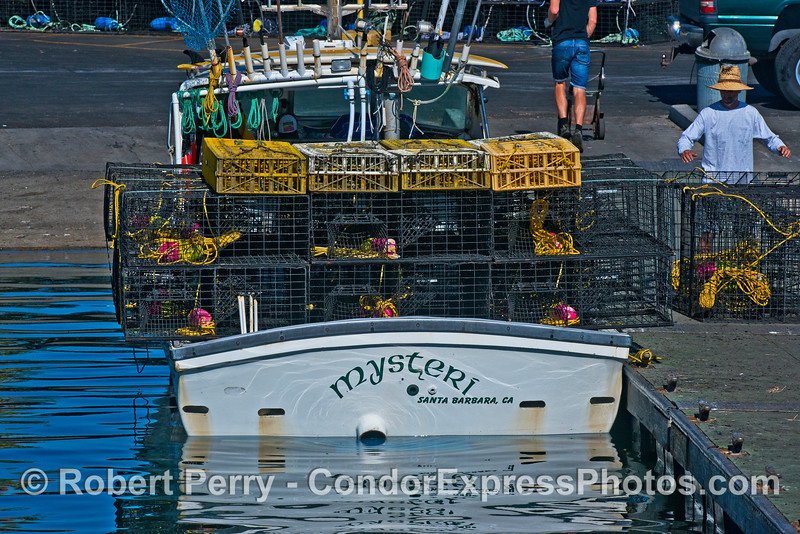 """Commercial lobster and crab vessel """"Mysteri"""" loads lobster traps (black cages) and crab traps (yellow plastic boxes) at the launch ramp in Santa Babara Harbor"""