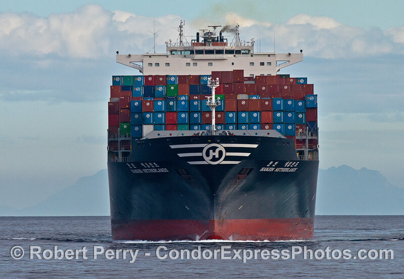 A head-on view of the bow of Hanjin Netherlands stacked with shipping containers.