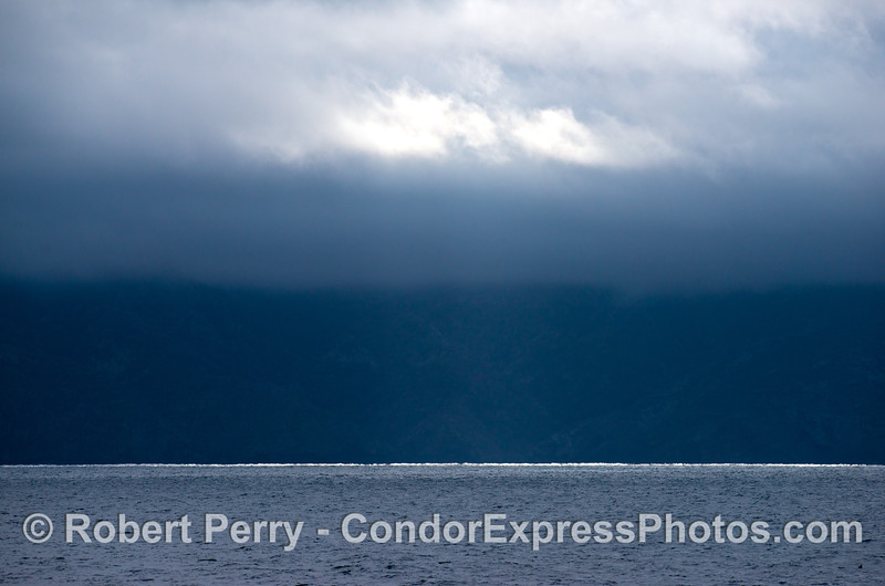 Santa Cruz Island in the rain with a streak of bright sunlight peakng through the clouds