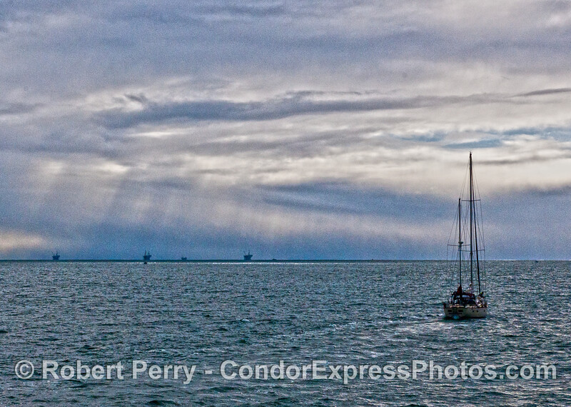 Rain squall with sailboat and offshore oil platforms