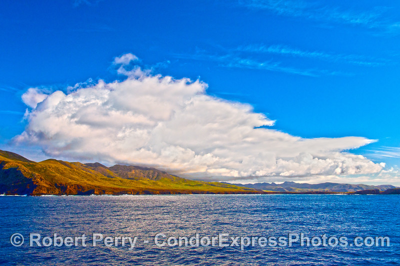 The newly green slopes along the far western edge of Santa Cruz Island are shown with majestic cloud formations.