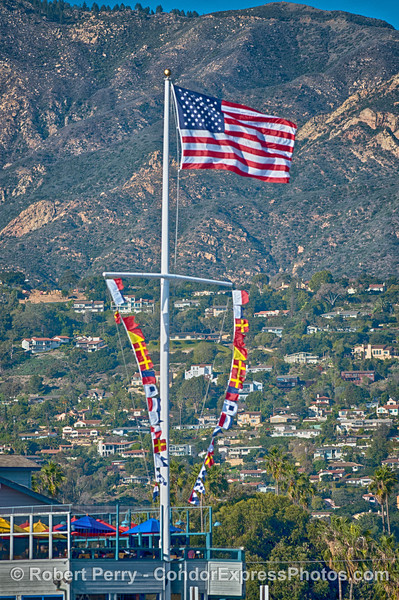A moderate breeze and the American Flag above Stearns Wharf, Santa Barbara Harbor.