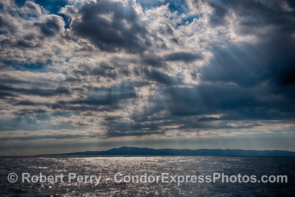 Storm clouds with breaks that let the sun shine through highlighting the Santa Barbara Channel and Santa Cruz Island