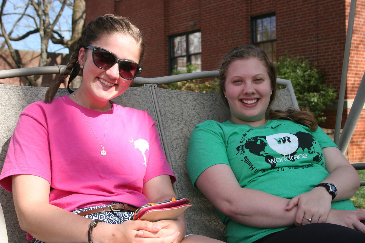 Two Gardner-Webb University students sitting on a swing in front of Decker Hall on a warm Spring afternoon.