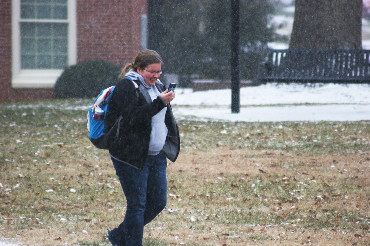A Gardner-Webb University student walks in the light snow covering the campus.