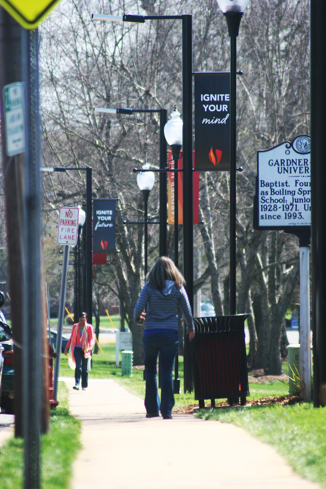 Gardner-Webb University students walking under the new banners on a Spring day.