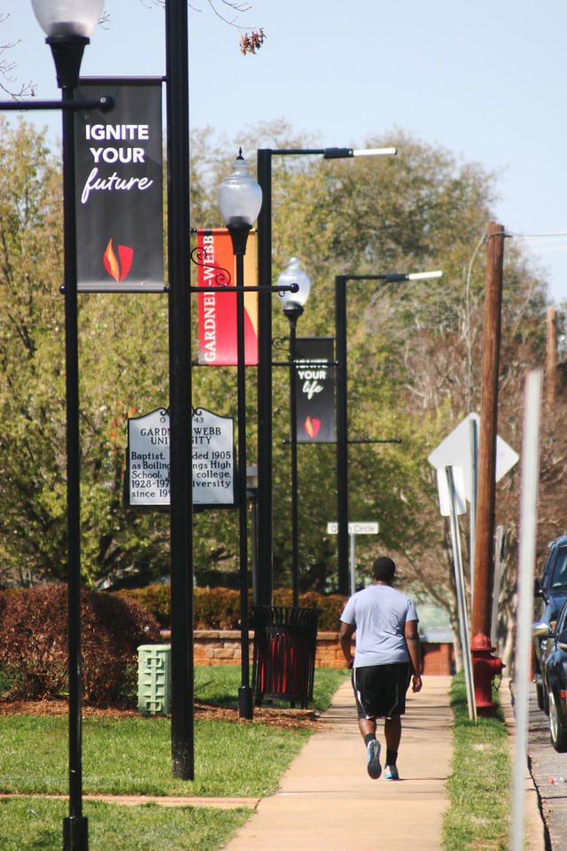 Gardner-Webb University student walking under the new banners on a Spring day.