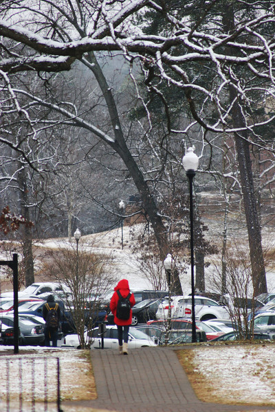 A Gardner-Webb University student walks across campus as the snow starts to cover the ground.