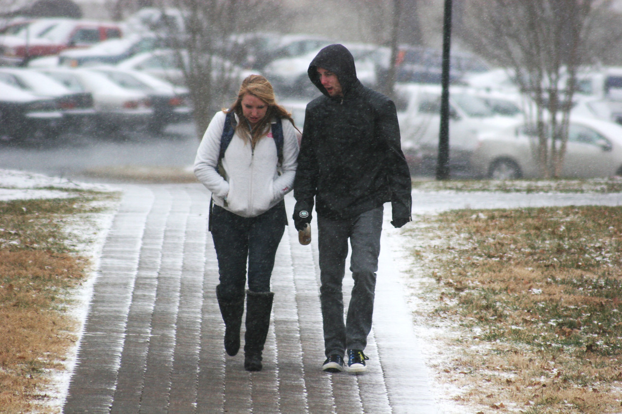 Gardner-Webb University students walks in the light snow covering the campus.