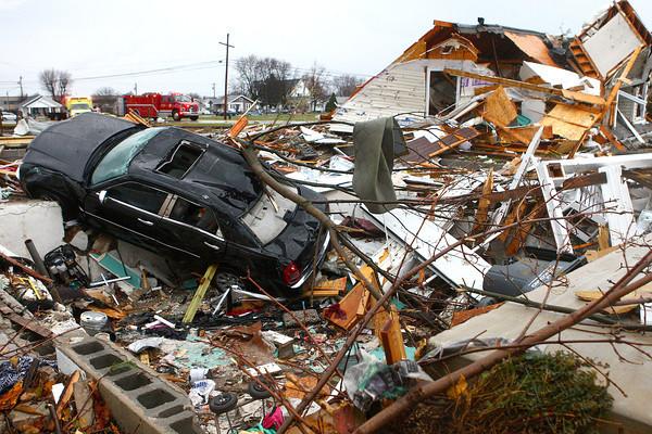 11-17-13<br /> Kokomo tornado damage<br /> A car sits halfway in a basement at a leveled home near Home Avenue and Hoffer Street.<br /> KT photo   Kelly Lafferty