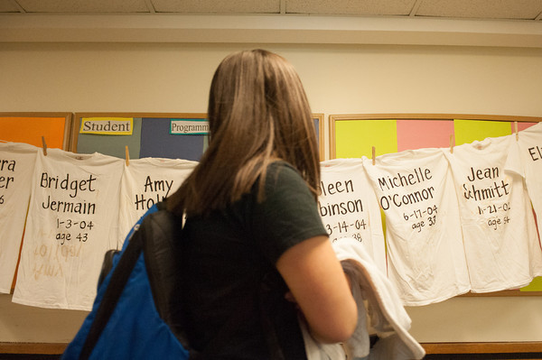 142408 Clothesline JOED VIERA/STAFF PHOTOGRAPHER-Sanborn, NY- A student looks as she passes by shirts with names of domestic violence victims on a clothesline  at NCCC April 8, 2014.