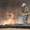 140410 Fire JOED VIERA/STAFF PHOTOGRAPHER-Lockport, NY-Ben Ripson A volunteer Firefighter with the South Lockport Fire Company stomps out a fire behind an apartment complex in the 6500 block of Lincoln Place April 10, 2014.