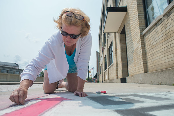 140806 JOED VIERA/STAFF PHOTOGRAPHER-Lockport, NY-Ellen Martin chalks the sidewalk outside of her shop Sweet Rides to promote chalkfest on Thursday, August 7th.