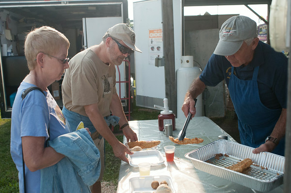 140801 JOED VIERA/STAFF PHOTOGRAPHER-Lockport, NY- Allen Lackey a Mason from Lodge #97 serves Bob and Diane Eshelman fish fry at the Niagara County Fair on Friday, August 1st.