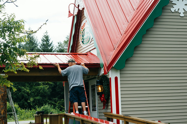 JOED VIERA/STAFF PHOTOGRAPHER-Lockport, NY- A contractor adds a gutter to Santa's Christmas Cottage's  new porch Tuesday, August 12th.