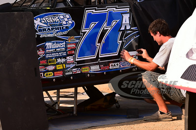 Justin Asplin crew member applies decals to his car